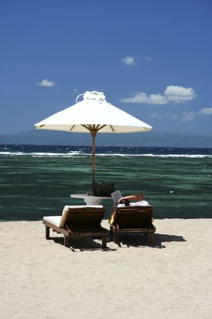 woman relaxing on sun lounger reading book on sanur beach, bali, indonesia photo