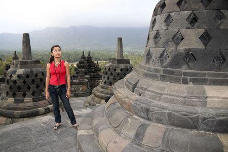 yogyakarta: asian woman tourist admires the borobudur ruins near yogyakarta in java indonesia