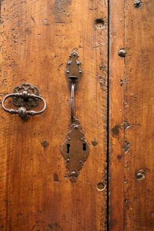 lourmarin: antique locks on woodworm riddled old wooden door in provence france