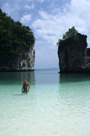 samll: male tourist wading in beautiful blue lagoon enclosed by karst cliffs on samll island near phuket and krabi in thailand