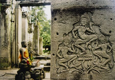 asparas or khmer dancing girls carved into walls of temple in angkor wat bayon with seated buddha behind Stock Photo
