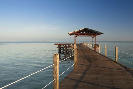 mabul: wooden jetty on mabul island looking across the ocean to sipdan island on the horizon sabah malaysian borneo Stock Photo