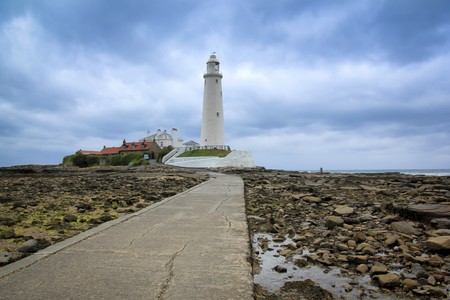 reached: st marys lighthouse in whitley bay on the northeast coast of england, first operational in 1898 and decomissioned in 1984 , the island is reached at low tide across a causeway Stock Photo