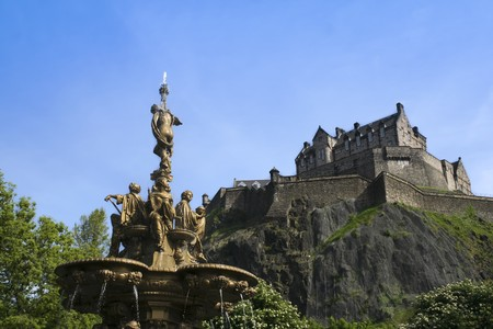 princes street: extinct volcano castle rock rising above the ross fountain in princes street gardens in edinburgh scotland