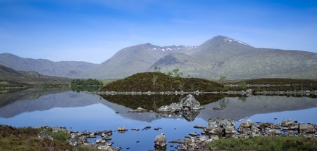 mountains reflecting in the still waters of lakes on rannoch moor in the scottish highlands Stock Photo