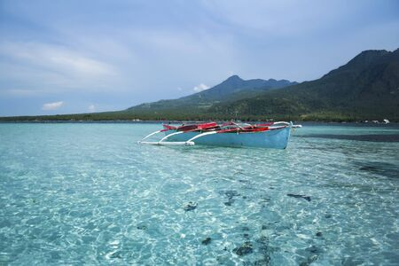 small outrigger traditional fishing boat in the clear seas of camiguin island near mindanao in the philippines photo