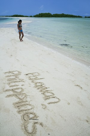 asian girl in bikini walking on beach with the words palawan philippines written in the sand photo