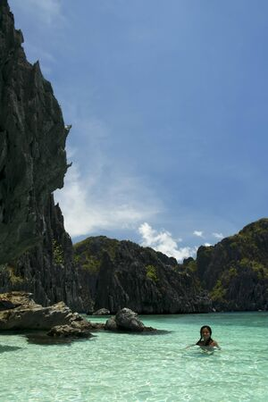 filipina woman swimming in the clear blue waters of el nido palawan island in the philippines photo