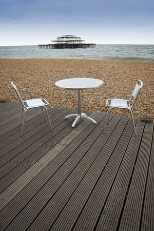 tabel and chairs on wooden decking of outdoor cafe on brighton beach east sussex england photo