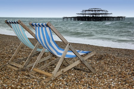 striped canvas deckchairs on brighton beach with the ruins of the west pier behind west suusex england
