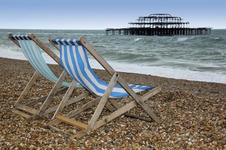Striped Leinwand Liegestühle am Brighton Strand mit den Ruinen der Westen Pier hinter Westen Suusex england  Standard-Bild - 7978105