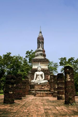 colonade: white seated buddha in the temple ruins of the ancient city of sukhothai in thailand