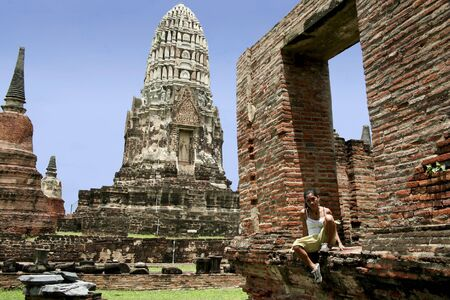 asian woman sitting in frame of collapsed building in the temple ruins of the ancient city of ayuthaya in thailand Stock Photo - 8029819