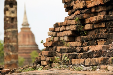 buddhist stupa: old crumbling overgrown birck wall in front of stupa in the temple ruins of wat mahathat in sukhothai historic park thailand