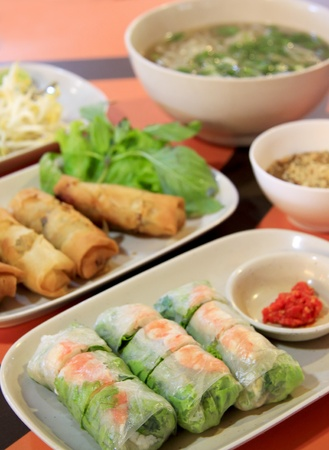 vietnamese summer rolls, fresh spring rolls with prawn served with chilli po noodle soup and fried spring rolls served at food court in bangkok thailand Stock Photo