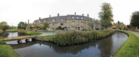 oxfordshire: panorama of the river eye winding through the quaint village of lower slaughter in oxfordshire england past cottages built in traditional cotswalds stone