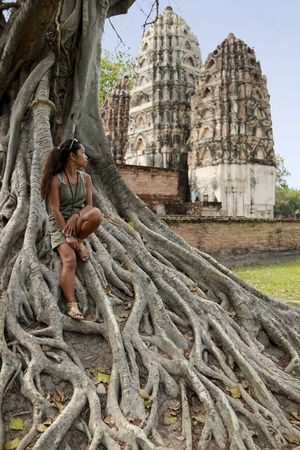 female tourist sitting on roots of large banyan tree in wat si sawai temple ruins sukhothai historical park thailand photo