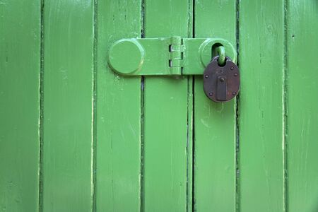 green painted wooden door closed with an old fashioned rusty metal padlock photo