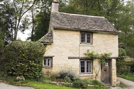 architecture detached house: small golden limestonoe cottage in the village of bibury in the cotswalds, gloucestershire, england