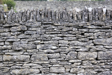 old english: traditional dry stone wall in cotswolds village of bilbury england
