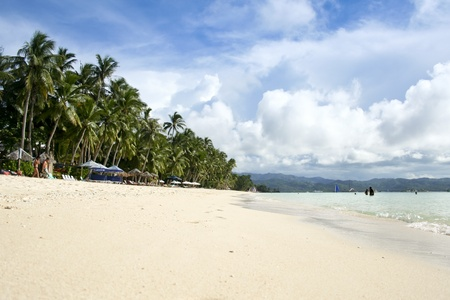 tourists having fun on the white sand beach of boracay island in the philippines