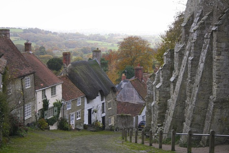 Old cottages line the steep cobbled road of gold hill in shaftesbury in dorset engalnd with views out to the Blackmore Vale beyond