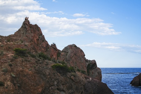 two young men sit on top of a rocky cliff overlooking the beach at theoule sur mer in the south of france photo