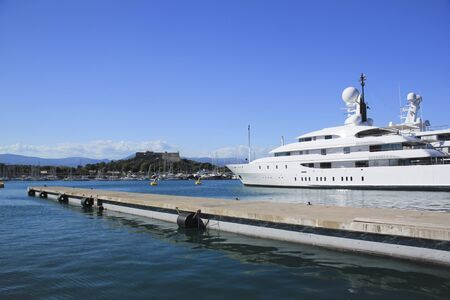 cote d'azure: white superyacht at anchor in antibes harbour overlooked by castle in the cote dazure in the south of france