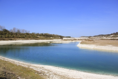 disused: blue sky reflected in the lake created in disused chalk quarry at pitstone cement works buckinghamshire with ivinghoe beacon behind Stock Photo