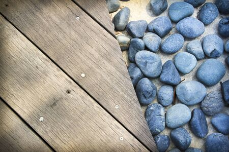 weathered wooden boards flloring next to smooth blue rocks photo