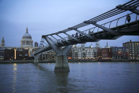 st pauls: people crossing the millenium bridge across the river thames in london uk at night