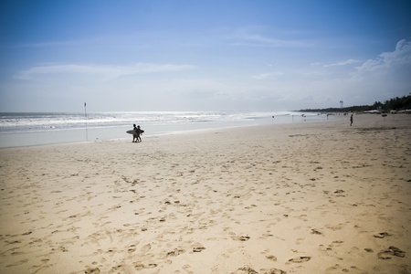 legian: couple walking along the shore of kuta beach, bali indonesia Stock Photo