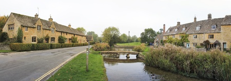 panorama of the river eye winding through the quaint village of lower slaughter in oxfordshire england past cottages built in traditional cotswalds stone  Stock Photo - 14247522