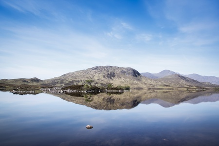mountains  reflecting in calm water of loch on rannoch moor in the scottish highlands photo