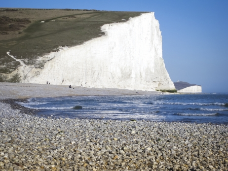 brighton beach: pebble beach and white chalk cliffs of the seven sisters at birling gap in sussex england