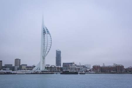 portsmouth: spinnaker tower and gunwharf quays shopping mall covered in clouds on an overcast day in portsmouth england