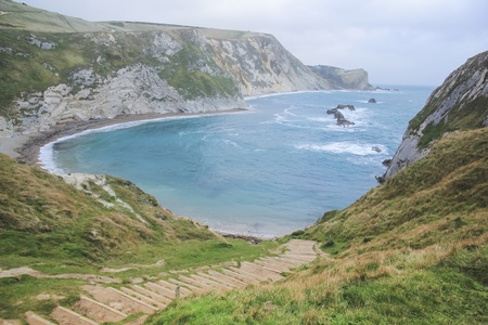 steep cliffs: steps leading down steep cliffs to durdle dor beach on dorset coastline lulworth england Stock Photo