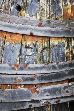 decayed: rusting metal hoops on decayed old wooden barrel