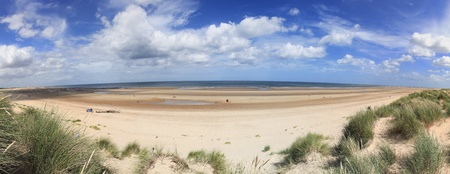 People enjoying summmer day on the beautiful sandy beach of Holkham in North Norfolk, England photo