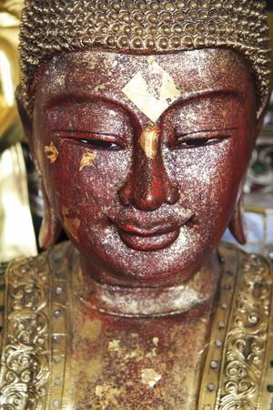 cabeza de buda: pan de oro aplicado a la cara de la estatua de Buda tallada elegante en templo budista de Bangkok Tailandia