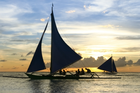 outrigger: tourists onboard paraw traditional outrigger sailing boats at sunset tours along the coast of boracay island in the philippines