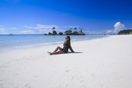 asian female sitting on white sand beach of boracay island in the philippines photo