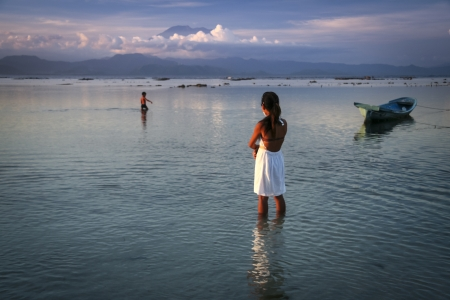 nusa: mother watching child playing in the sea off nusa lembongan island at sunset with gunung agaung volcano on bali behind