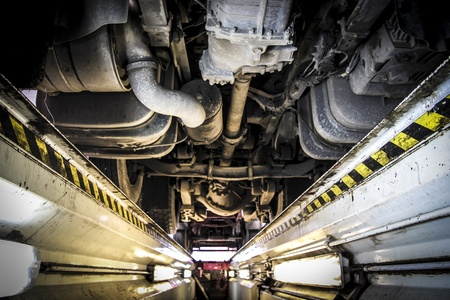 repair garage: underneath of a truck as seen from vehicle inspection trench