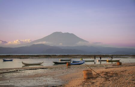 skiff: local collecting seaweed farmed on the reefs of nusa lembongan island off bali in indonesia with the gunung agung volcano behind