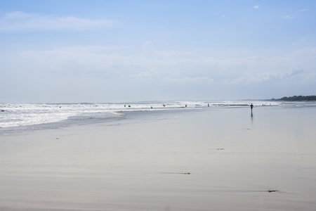 woman walking past surfers on vast sands of kuta beach in bali indonesia photo