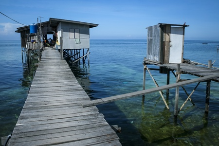 mabul: stilt house in fishermans village on mabul island sabah borneo with toilet over the ocean