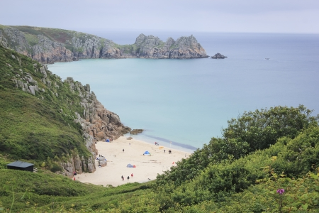 porthcurno: tourists on small sandy porthcurno beach in cornwall england