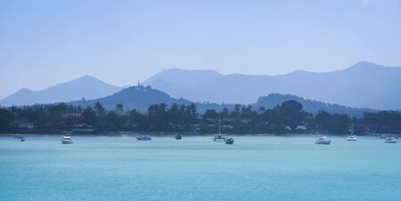 panoramic view of koh samui island coastline at dawn with hilltop temple in chaweng behind photo