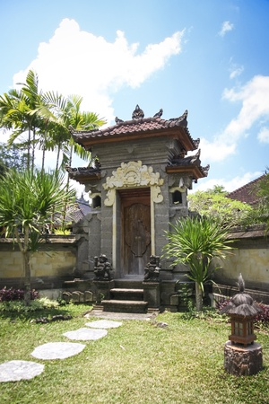 garden gate: ornate raised stone gate in tropical garden with stepping stones ubud bali indonesia